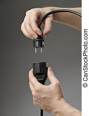 Extension cord - Hand plugging a black european extension...