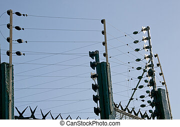 extensive green electric fence surrounding residential property