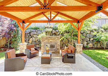 Exterior covered patio with fireplace and furniture. Wood...