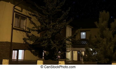 Exterior of a smart house illuminated gradually in every...