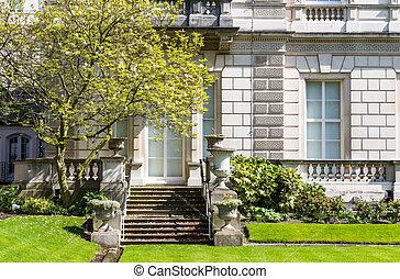 Exterior View and Garden Lawn of a Beautiful Old Rural English Cottage House, front yard lawn, flowers blooming in the spring
