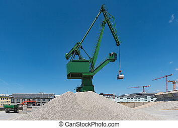 Exterior view of a cement factory with green crane