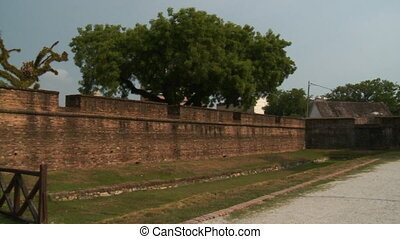 Wide low-angle panning shot of the external brick walls of Fort Cornwallis with gun defence openings, a tarmac ked road, tree silhouettes, and roofs of old buildings, Fort Cornwallis, Georgetown, Penang, Malaysia