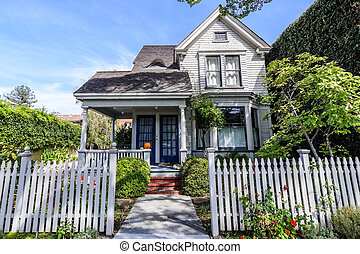 Exterior view of wooden house surrounded by a white fence in one of the residential areas of Palo Alto, south San Francisco bay area