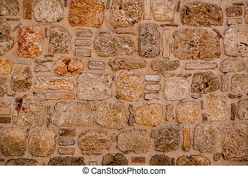 exterior wall with masonry of natural stone blocks of shell rock of different shapes