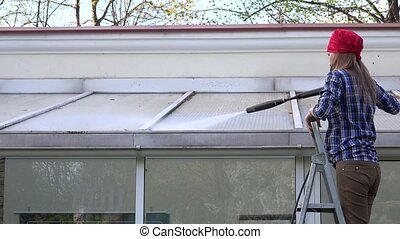 Exterior washing and building cleaning glass roof with high pressure water jet.