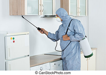 Exterminator In Spraying Pesticide In Kitchen - Side view of...