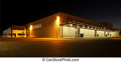 External wide angle view of modern warehouse at night - wide...