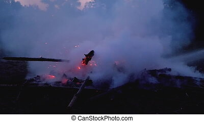 Extinguish a Fire with Water by a Firehose in Slow Motion 180 fps. Put out a forest campfire at evening. Big Campfire of the Branches Burn at Night. Lot of smoke from the fire extinguished.