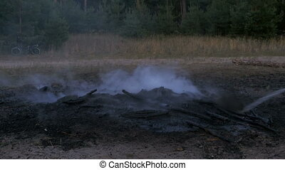Extinguish a Campfire with Water by Hose. Fire Fighter hold...