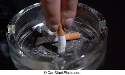 Hand extinguish a cigarette in an ashtray close-up.Slow motion