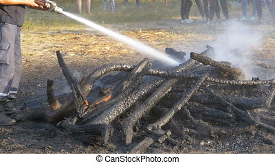 Extinguish a Fire with Water by a Firehose. Firefighter hold...