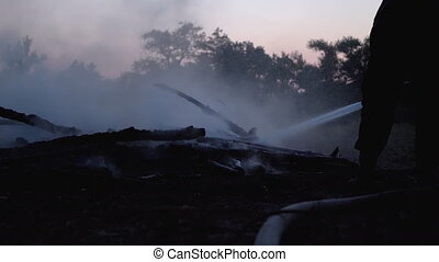 Extinguish a Fire with Water by a Firehose. Firefighter hold a hose and put out a forest campfire at evening. Big Campfire of the Branches Burn at Night. Lot of smoke from the fire extinguished