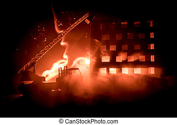 extinguish the fire of a private house at night. Toy fire truck with long ladder and burning building at night. Fire alarm concept.