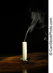 Extinguished candle against black