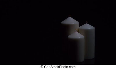 Three extinguished candles with smoke on a black background.