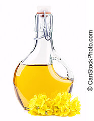 Extra virgin oil in a bottle with rapeseed flowers isolated...