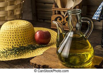 Extra virgin olive oil in glass cruet in a rustic kitchen, ...