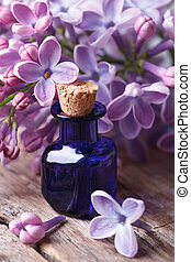 Extract from the fragrant lilac flowers close up on the table