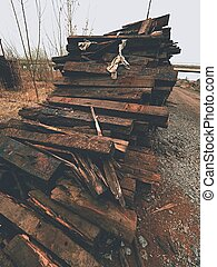 Extracted old wooden ties in stock. Old oiled used oak railway sleepers stored after big reconstruction of old railway station.