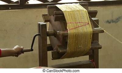 A hand held, medium shot of a crafty person extracting the silk wires on a wheel.