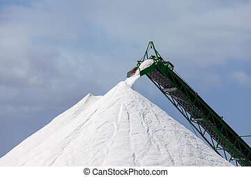 Extraction of salt. Salt mountains on blue sky.
