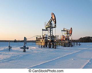 Oil pump jack in work. Oil industry in West Siberia. Siberian frost in sunny day.