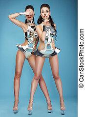 Extravagance. Two Heeled Women in Futuristic Clubwear....