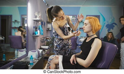 Extravagant girl in a black dress and with the red color of hair in a beauty salon.