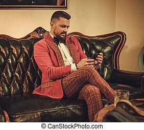 Extravagant stylish man sitting on classic leather sofa in gentleman club