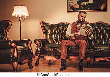 Extravagant stylish man sitting on classic leather sofa in...