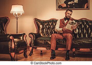 Extravagant stylish man sitting on classic leather sofa in...