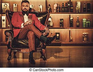 Extravagant stylish man with whisky glass sitting on...