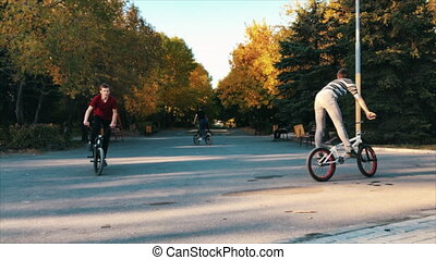 Extreme bmx biker pedals and jumping with tricks in a sunny...