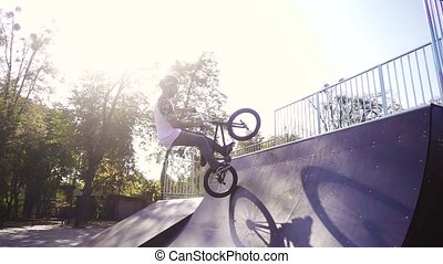 Extreme bmx biker performing a trick on the skatepark, slow motion
