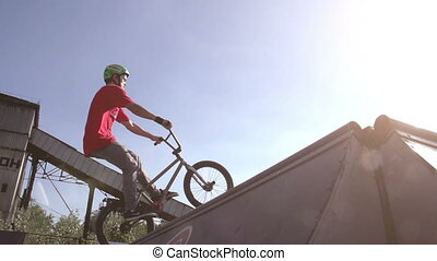 Two young men perform stunts on bikes. Slow Motion at a rate of 240 fps