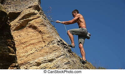 Extreme Climber Climbing A Rope From A Rock