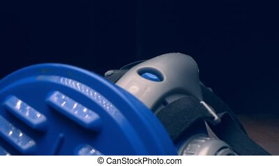 extreme close-up, detailed. blue respirator with thick white smoke on a black background