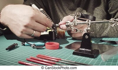 Male hands repairing wire for electronic devices. - Extreme...