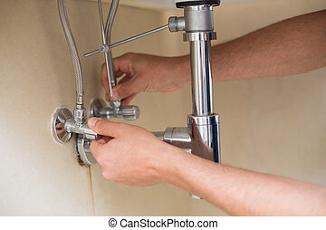 Extreme Close up of a plumber's hands and washbasin drain