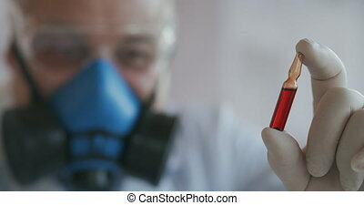 Extreme Close-up of a scientist in a blue respirator and protective glasses, a developer of a coronavirus vaccine holding a red ampoule. The doctor looks at the new vaccine. A new type of virus medicine. High quality 4k footage