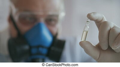 Extreme Close-up of a scientist in a blue respirator and protective glasses, the developer of the coronavirus vaccine is holding a white transparent ampoule. The doctor looks at the new vaccine. High quality 4k footage