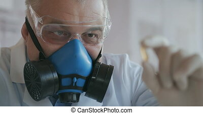Extreme Close-up of a scientist in a blue respirator and protective glasses who developed a coronavirus vaccine holding a white pill. The doctor looks at the painkillers antiviral medication. Vitamins. High quality 4k footage