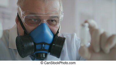 Extreme Close-up of a scientist in a blue respirator and protective glasses who developed a coronavirus vaccine holding an ampoule of white powder. Narcotic substances and painkillers. High quality 4k footage