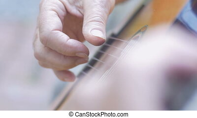 Extreme close up of a senior man's hands finger picking and playing guitar