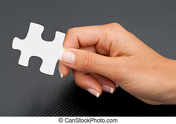 Extreme close up of hand holding puzzle piece.