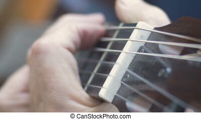 Extreme close up of healthy aging fingers playing chords on guitar