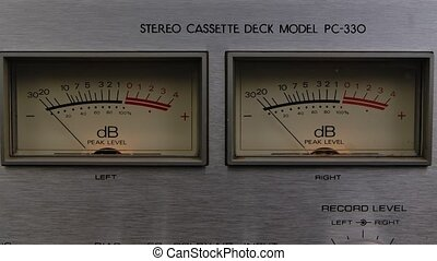Extreme close up of indicator dB decibel meter needle movement reading level going up and down on vintage electronic sound audio device. Dashboard on tape recorder. Slow motion