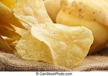 extreme close up of potato crisps on a jute fabric