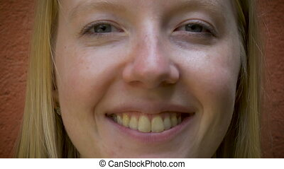 Extreme close up portrait of a young woman smiling at the camera